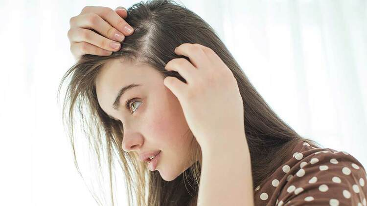 Female examining hair loss