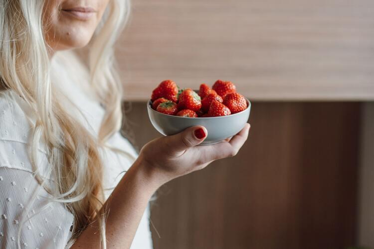 woman long healthy hair eats berries