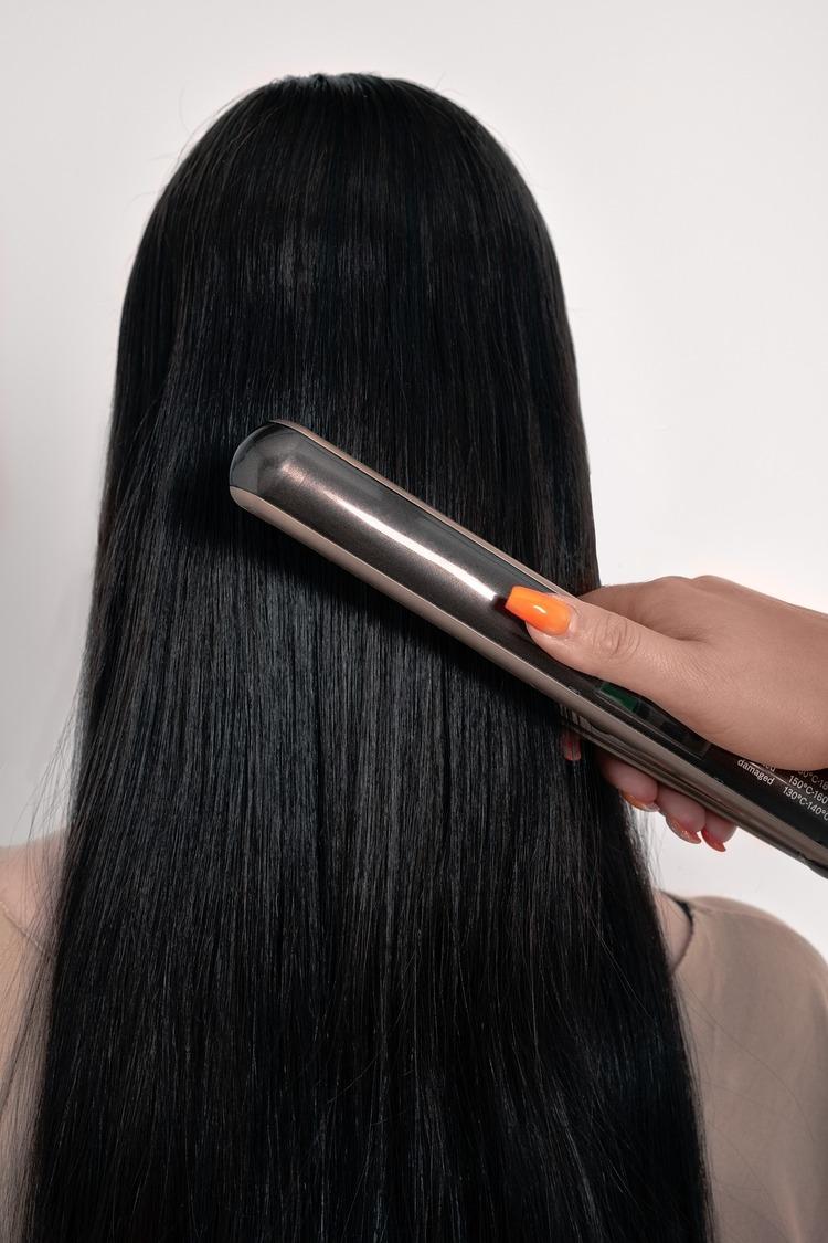 Brunette getting her hair straightened
