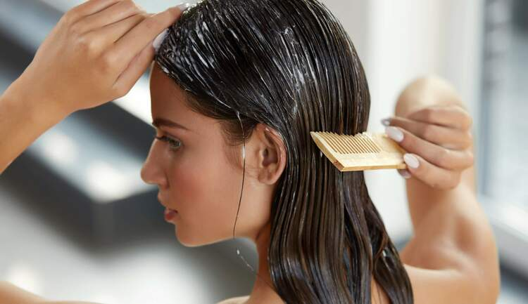 woman combing hydrating hair mask through hair